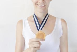 mulher segurando medalha de ouro foto