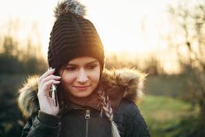 jovem ligando com o celular ao ar livre no inverno foto