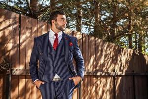 homem contra uma cerca de madeira em um terno elegante.