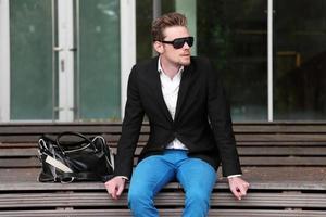 homem sentado do lado de fora usando óculos escuros foto