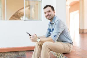 blogger publicando postagem no site usando o telefone celular na entrada foto
