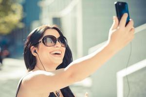 Linda mulher de negócios elegante de cabelo preto comprido usando smartphon foto