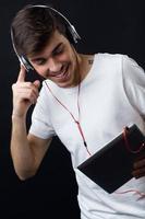 jovem bonito ouvindo música. isolado no preto.