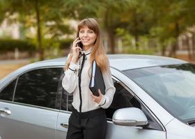 empresária no carro ao telefone.