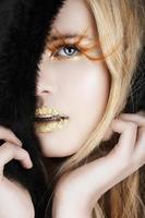 folha de ouro e cílios postiços em uma mulher loira