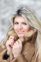 jovem mulher com casaco de pele no inverno ao ar livre. foto