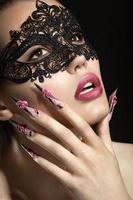 linda garota em uma máscara com unhas compridas.