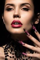 linda garota com unhas compridas e lábios sensuais. rosto bonito foto