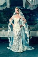linda noiva em pé no meio do salão de banquetes foto