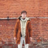 homem da moda ao ar livre em estilo urbano contra uma parede de tijolos foto