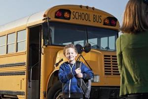 menino na frente do ônibus escolar foto