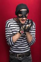 ladrão feliz segurando colar roubado foto