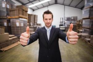 gerente de armazém sorrindo para a câmera mostrando o polegar para cima