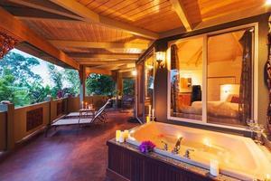 deck romântico em casa tropical com banheira e velas