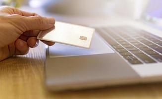 mão segurando um cartão de crédito dourado ao lado do laptop