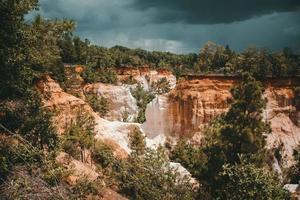 formação de rocha marrom sob céu tempestuoso foto