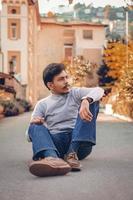 jovem sentado na estrada foto