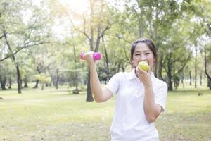 mulher se exercitando e comendo uma maçã foto