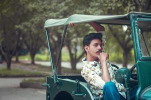 homem sentado em um carro antigo