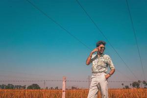 homem de óculos escuros ao lado da cerca e do campo foto