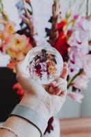 pessoa segurando uma bola de lente na frente de flores foto