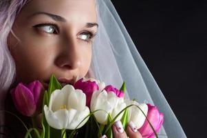 rosto de mulher com um buquê de tulipas foto