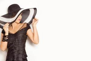 menina da moda com um grande chapéu no fundo branco foto