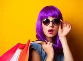mulheres com cabelo violeta com sacolas de compras. foto