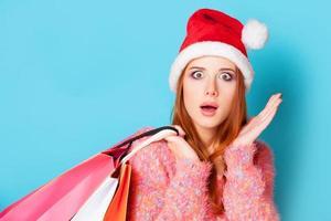 garota ruiva com sacolas de compras em fundo azul. foto
