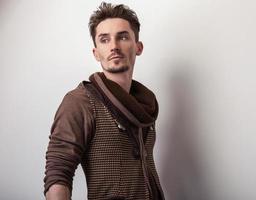 jovem atraente em uma pose de suéter marrom no estúdio. foto