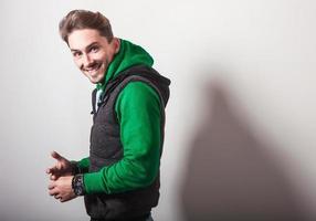 jovem atraente em colete cinza e suéter verde.