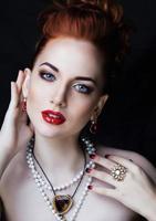 mulher ruiva elegante beleza com penteado e manicure usando jóias foto