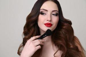 jovem com cabelo escuro luxuoso e maquiagem de noite foto