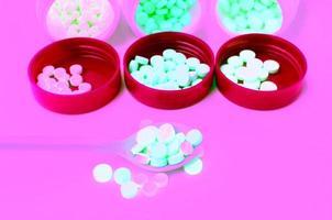 comprimido de medicamento colorido na colher e frasco aberto foto