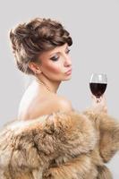 Mulher bonita elegante vestindo um casaco de pele marrom e bebendo vinho foto