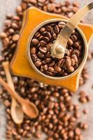grãos de café e moedor de café antigo foto