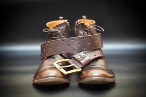 sapatos masculinos de couro e um cinto de couro com fivela foto