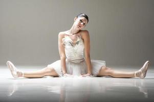 jovem linda bailarina esticando as pernas no chão do estúdio