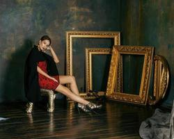 mulher morena rica beleza no interior de luxo perto de quadros vazios foto