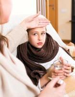 mãe cuidando da filha doente foto
