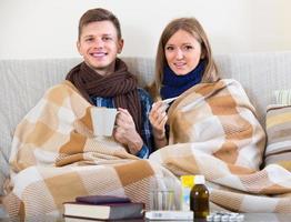 casal sentado sob um cobertor com um livro foto