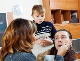 esposa amorosa e filho cuidando de homem doente foto