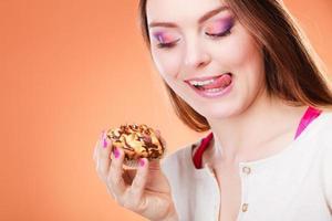 mulher segura bolo na mão lambendo os lábios