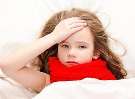 menina doente deitada na cama foto