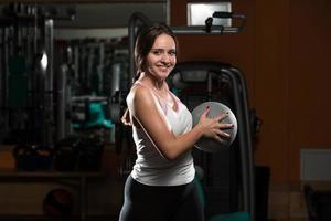 jovem mulher treino com bola médica foto