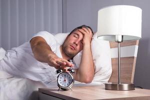 homem cochilando despertador foto