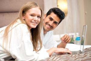 casal jovem sorridente usando laptop na cama em casa foto