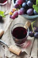 vinho tinto e uva na mesa de madeira