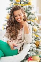 jovem feliz usando o controle remoto da TV perto da árvore de Natal foto