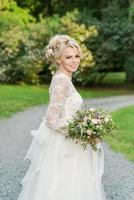 linda noiva loira no parque com buquê de casamento foto